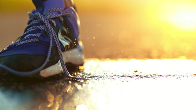slo mo untied running shoe splashing on wet road - untied stock videos and b-roll footage