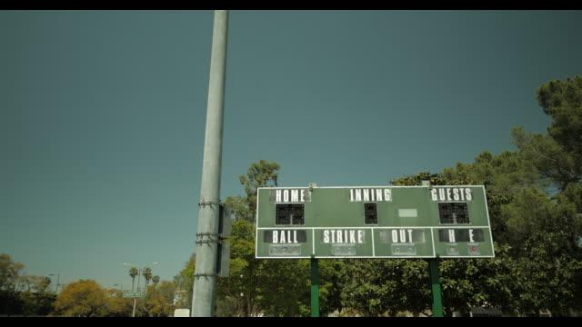 unused scoreboard at empty baseball diamond, no people, during april 2020 covid-19 - baseball diamond stock videos & royalty-free footage