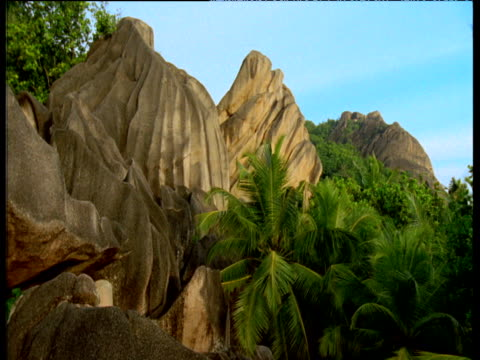 Unusual multicoloured rock formations by lake surrounded by palm trees, Seychelles