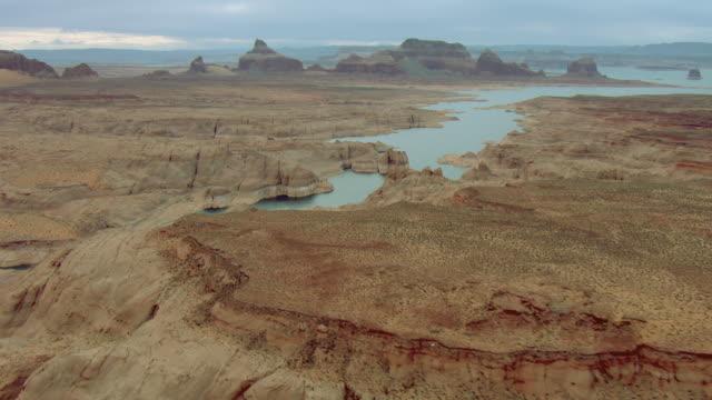 vídeos de stock e filmes b-roll de unusual sandstone formations tower above the desert near a lake. - chaminé de fada