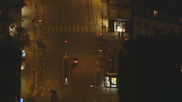 Unusual static shot showing a quiet junction next to the métro staion of Saint Placide on the rue de Rennes at night, Notre-Dame-des-Champs (6th arrondissement), Paris, France.