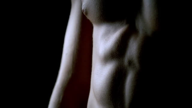 vidéos et rushes de cu tu up abdominal muscles and across chest of muscular man against black background/ new york, new york  - plaisir
