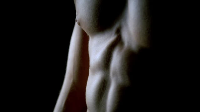 cu tu up abdominal muscles and across chest of muscular man against black background/ new york, new york  - torso stock videos & royalty-free footage