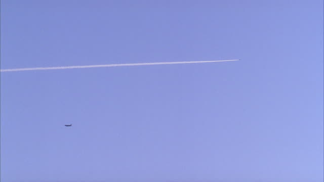 up angle of airplanes flying in sky leaving exhaust trail behind.