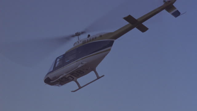 vidéos et rushes de up angle of blue and gold helicopter. see helicopter fly over head. see sparks from helicopter. see smoke rise from helicopter and small explosion near rudder. thick smoke rises, helicopter moves left over rocky hill, could be crash. - hélicoptère