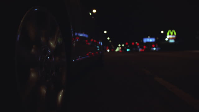 up angle of car driving. see view from front bumper close to pavement as car drives along night street. lights and reflections visible. see police car with sirens in bg following and overtake car. pan left to right as police car drives past. - following moving activity stock videos & royalty-free footage