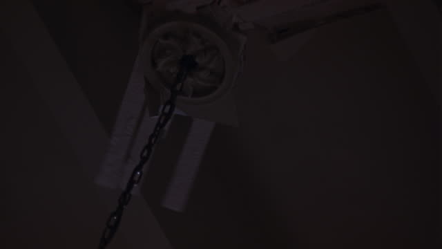 up angle of ceiling with chandelier chain pulled out and hanging by two electrical wires. mounting broken and turns back and forth as if weight is pulling on chandelier from off screen. wires hang out of junction box and wood and plaster falls. - holzkiste stock-videos und b-roll-filmmaterial