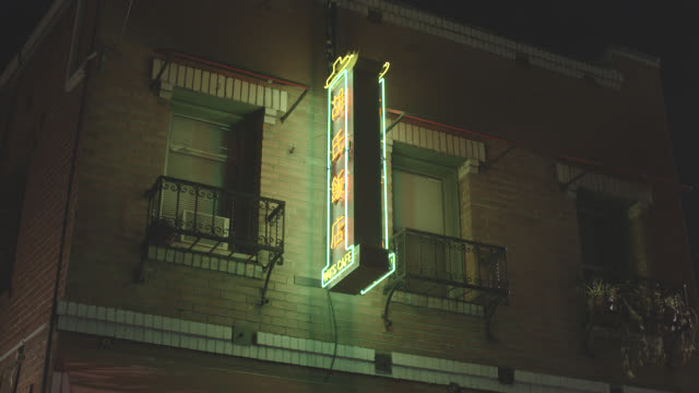 up angle of neon sign for chinese restaurant on brick building.