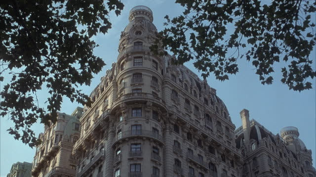 up angle of ornate stone apartment building or ansonia hotel in the upper west side of manhattan. see tree branches hanging down in top foreground.