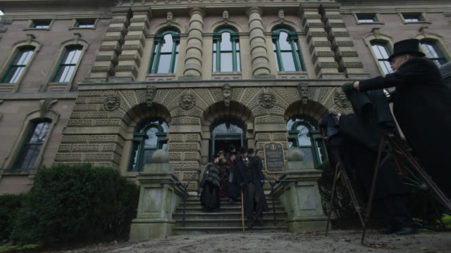 up angle of people leaving fall river massaschusettes superior courthouse. men with cameras and top hats visbile outside. could be reporters.