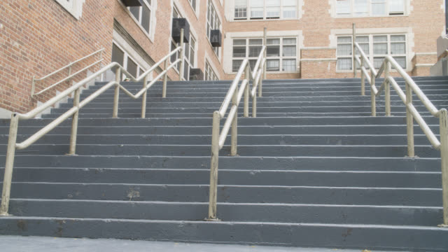 stockvideo's en b-roll-footage met up angle of stairs at school as children come running out of building. - school building