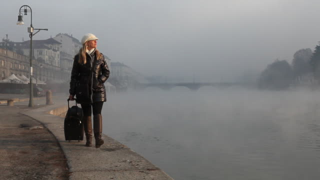pan up at business woman walks along river, with luggage - schiebermütze stock-videos und b-roll-filmmaterial