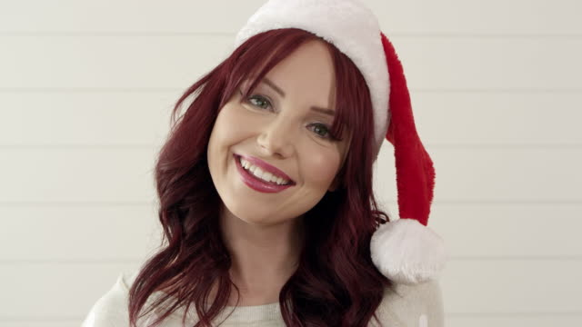 up close of attractive red headed woman wearing christmas stocking hat - weihnachtsmütze stock-videos und b-roll-filmmaterial