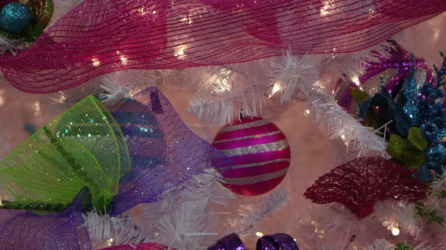 up close pan of colorful decorations on white christmas tree - ribbon sewing item stock videos & royalty-free footage