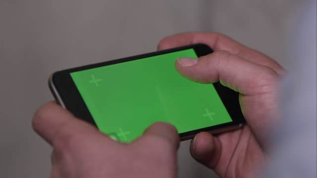 up close shot of someone using smartphone with green screen. - horizontal stock videos & royalty-free footage