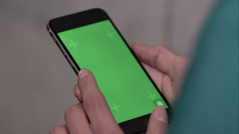 vídeos y material grabado en eventos de stock de up close shot of someone using smartphone with green screen. - verde color