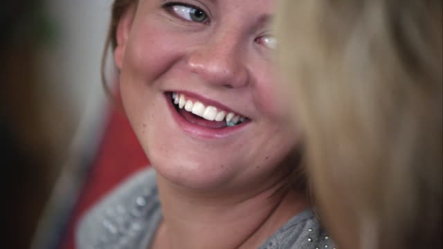 up close slow motion of girl smiling while conversing with another person. - gomma da masticare video stock e b–roll