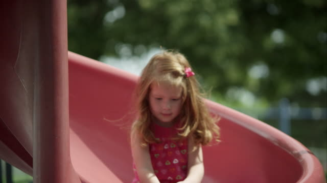 up close slow motion of red headed girl coming down slide in park. - rutschen stock-videos und b-roll-filmmaterial