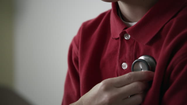 up close slow motion of stethoscope on young boys chest as he breaths in and out. - stetoscopio video stock e b–roll