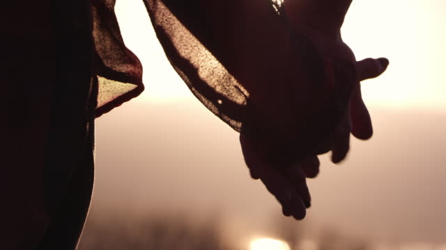 up close view of couple reaching to hold hands - silhouette stock videos & royalty-free footage