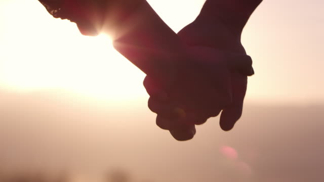 stockvideo's en b-roll-footage met up close view of couple reaching to hold hands - back lit