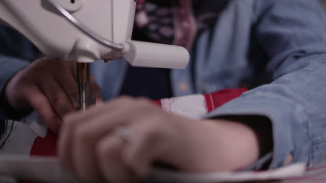 up close view of hands feeding flag throug sewing machine - made in the usa short phrase stock videos & royalty-free footage