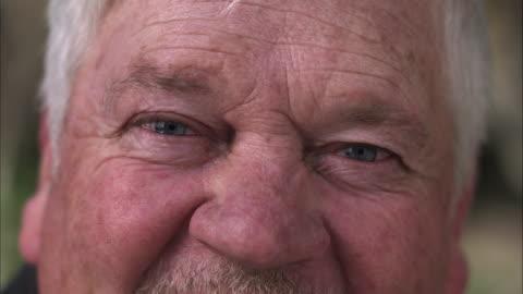 vídeos y material grabado en eventos de stock de up close view of older mans watering eyes. - viejo