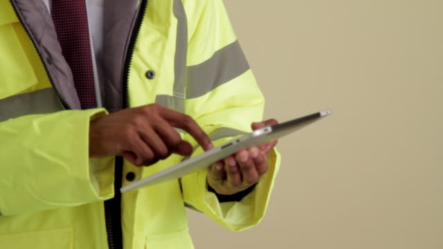 CU TILT up construction supervisor using tablet looking up and smiling at camera