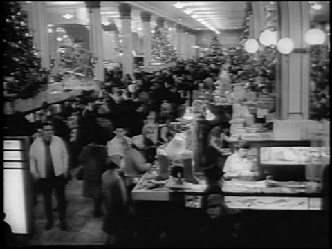 B/W 1964 up escalator point of view of busy department store at Christmas time / newsreel