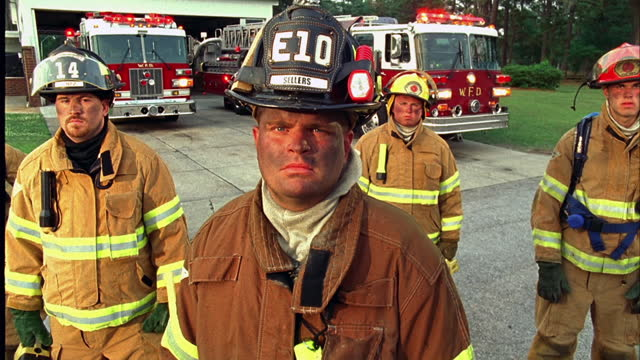 MEDIUM CRANE SHOT up portrait dirty firefighter in gear / others and fire trucks in background\n