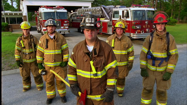 medium crane shot up portrait of group of firefighters in gear standing in front of fire trucks and station\n - heroes stock videos & royalty-free footage