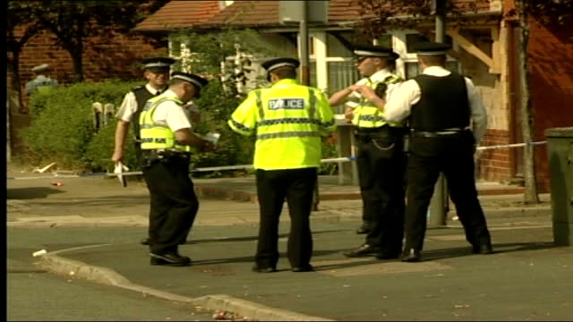 stockvideo's en b-roll-footage met up to 40 white and asian men involved violent brawl in preston; england: preston: callon estate: ext group of police officers stand in suburban road... - bord weg afgesloten