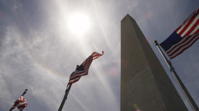 vídeos de stock, filmes e b-roll de up-angled view of the washington monument and flags with sun glare. shot in 2012. - artbeats