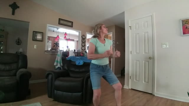 upbeat woman dances in her home while video chatting. - old stock videos & royalty-free footage