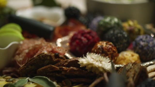 up-close shot of an appetizer charcuterie meat/cheeseboard with apple slices, cheese balls, prosciutto, crackers, garnishes, and cheeses at an indoor celebration/party - silver platter stock videos and b-roll footage
