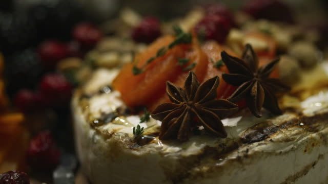 Up-Close Shot of Baked Brie Cheese, Dried Apricots, Thyme, and Star Anise on an Appetizer Plate at an Indoor Celebration/Party