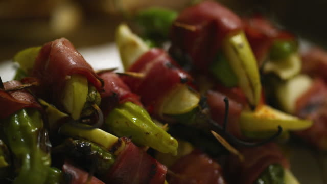 up-close shots of prosciutto wrapped shishito pepper and apple on an appetizer plate at an indoor celebration/party - appetizer stock videos & royalty-free footage