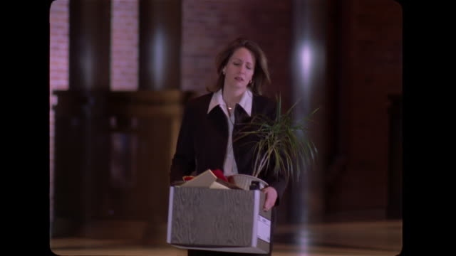 upon losing her job, a  businesswoman cries as she carries a box of her belongings through the lobby of her office building. - downsizing stock videos & royalty-free footage