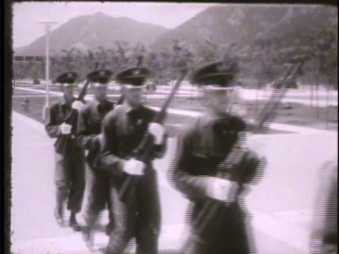 upper classmen, officers, supervising first year cadets marching w/ rifles across cadet area, cadets running w/ rifle. vs cadets jogging in... - 士官候補生点の映像素材/bロール