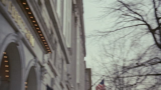 pan upper edge of a government building with colonnade, bare branches and lamp pole with banners, and entrance arches of the old ebbitt grill / washington, d.c., united states - メタルグリッド点の映像素材/bロール