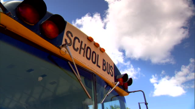 upper front of parked school bus w warning lights near roof