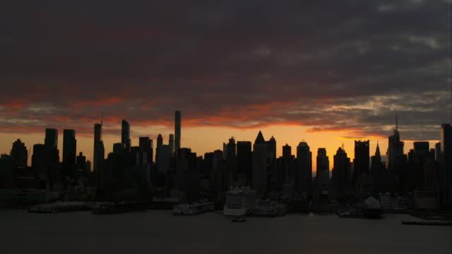 upper manhattan skyline silhouetted during early sunrise. - エスタブリッシングショット点の映像素材/bロール
