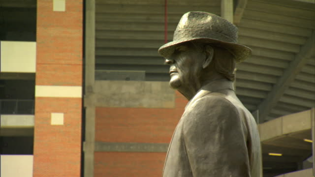 upper torso profile of coach paul w. bear bryant statue, statue w/ stadium bg. iconic, college football, trademark hounds tooth hat. - torso stock videos & royalty-free footage