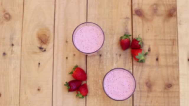 upper view of strawberry smoothies with chia seeds on a wood table. - strawberry milkshake stock videos & royalty-free footage