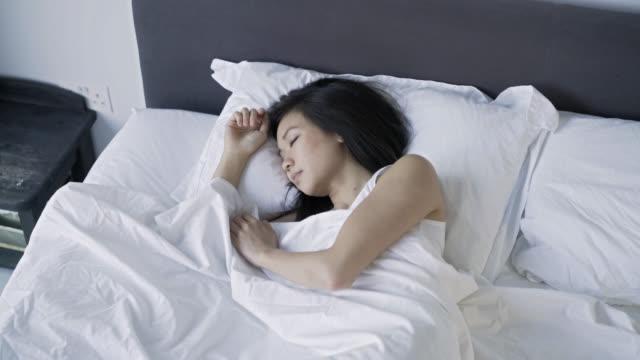 vidéos et rushes de vue supérieure de femme allongée émouvante d'un côté à l'autre - lit ameublement