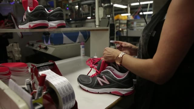 Uppers for New Balance Athletic Shoe Inc trainers are placed into a machine before their soles are attached during the manufacturing process at the...