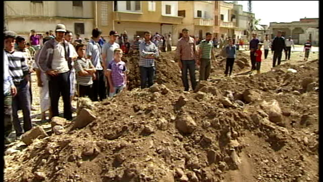 america accuses syrian regime of lying about houla massacre; houla: int man with bandaged arm stump ext gvs people beside mass grave man speaking sot... - 大量殺人点の映像素材/bロール