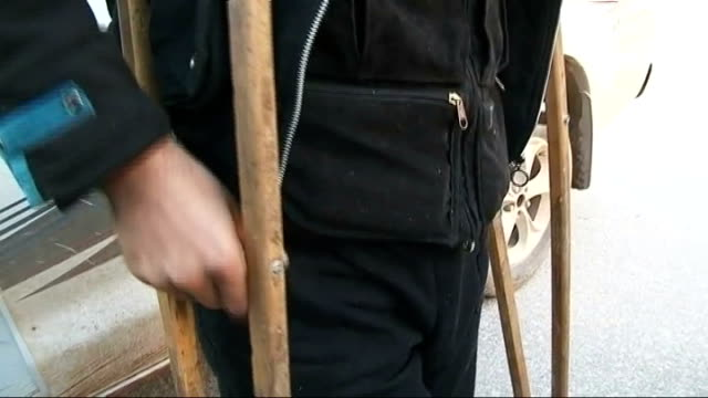vídeos de stock, filmes e b-roll de fighting continues in idlib gvs people along in town man on crutches with brace on leg rugman sitting with 'hasan' and hasan showing scar from... - brace