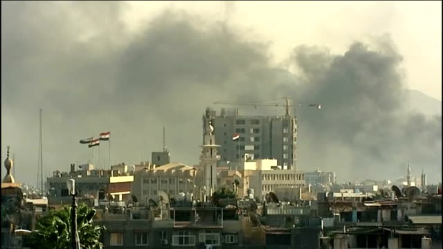 Government forces drive rebels out of Damascus SYRIA Damascus EXT Lorries and cars queuing on road PAN government tanks blocking other road Fire...