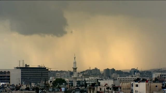 reports of more killings of protesters Damascus Dark clouds in sky TILT DOWN city City skyline Framed photographs of Syrian President Bashar alAssad...